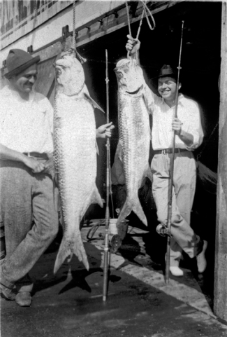 EH8128P 1928 Ernest Hemingway and John Dos Passos pose with two tarpon fish, Key West, 1928. Photograph in the Ernest Hemingway Collection of the John F. Kennedy Presidential Library and Museum, Boston.