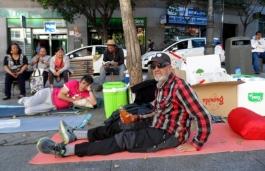 No es un indigente, es un activista del Sindicato Andaluz de Trabajadores, en huelga de hambre, protestando en Lavapiés el pasado mayo por la condena a prisión de Andrés Bódalo. Este había agredido a un concejal socialista hace unos años. La condena fue excesiva y el propio agredido pidió su absolución, sin éxito.