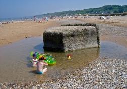 Sobre la playa de Arromanches-les-Bains juegan unos niños.